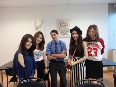 4 female students and their English teacher posing in a classroom